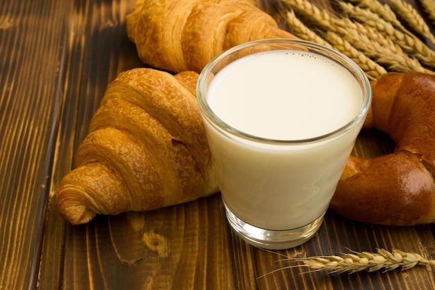 木製の背景に牛乳やベーカリー製品