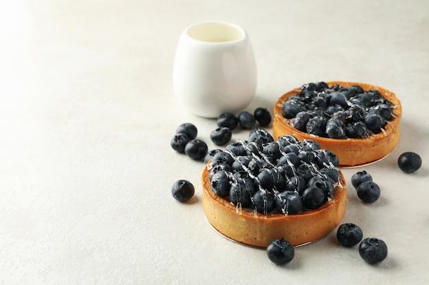 灰色のテーブルに牛乳とブルーベリーのパイ
