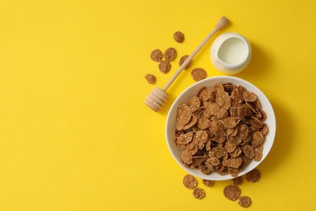 ミルクとミューズリーのボウルに黄色の背景