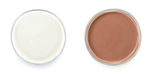 Молоко и шоколадная лужа молока в стекле, изолированные на белом фоне, вид сверху