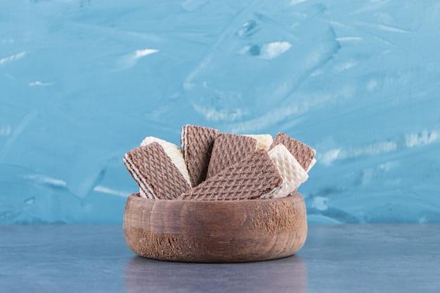 大理石の表面のボウルにミルクとチョコレートのウエハース