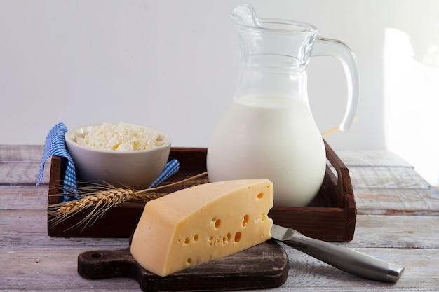 우유와 유제품은 소박한 스타일의 갈색 나무 쟁반에 서 있습니다