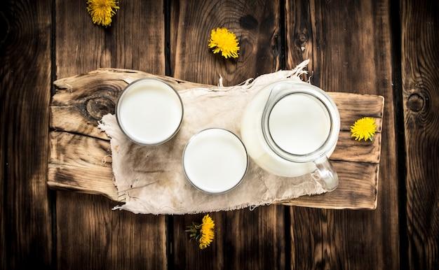ボード上のミルクとタンポポの花。木製のテーブルの上。
