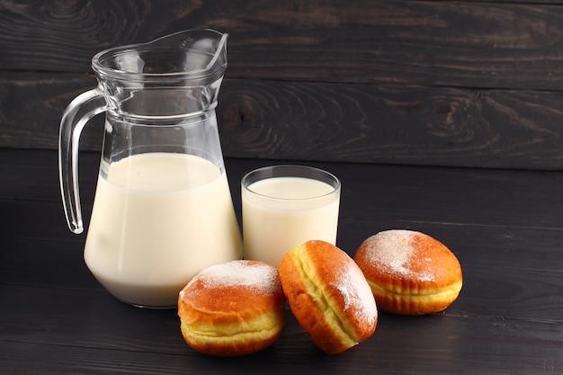 Молоко и пончик на темной поверхности
