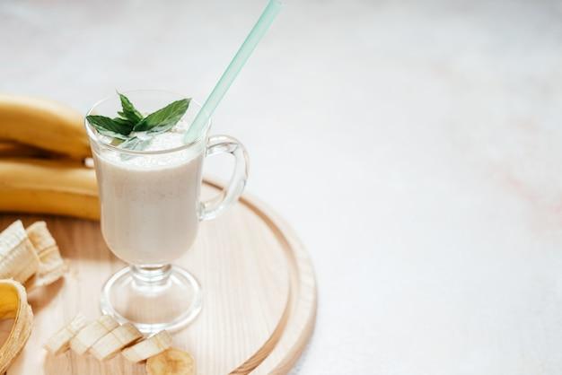 Молочно-банановый коктейль, украшенный листьями мяты, в стакане для латте с ручкой на светлой поверхности с копией пространства