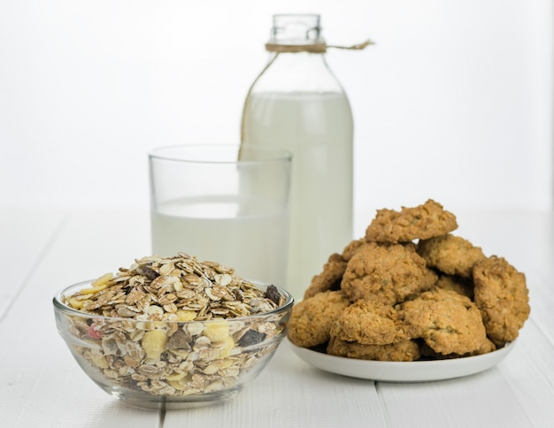 Milk bottle, bowl with muesli and fresh baked cookies on a white wooden table.