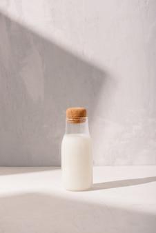 Бутылка молока на белом столе