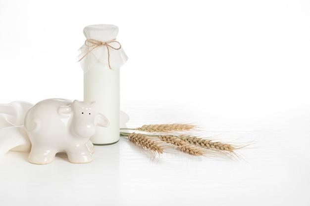 흰색 나무 테이블, 밀 귀 및 흰색 암소 입상에 우유 병