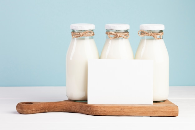 Milk bottles and card on chopping board
