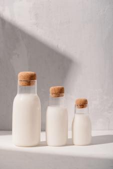 Бутылки молока на белом столе