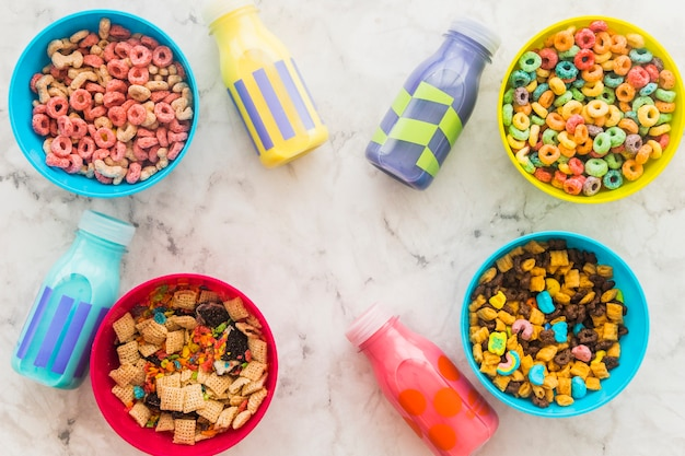 Milk bottles with bowls of cereal on table