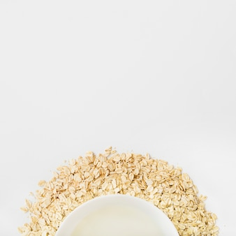 Milk bowl over the oat flakes on white background