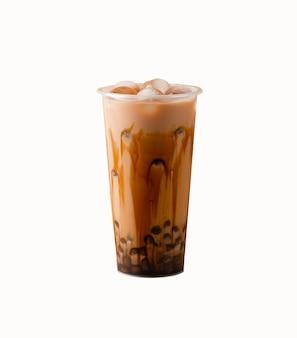 흰색 배경에 있는 플라스틱 컵에 타피오카를 넣은 우유 거품 차는 선택적 초점을 분리합니다