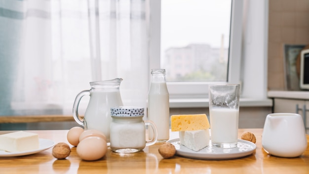 Milk; cheese; eggs and nuts on a wooden table in kitchen