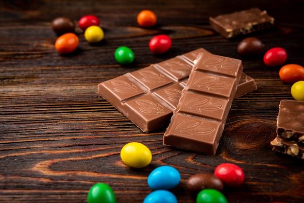 어두운 나무 테이블에 밀크 초콜릿 및 색상 당의정.