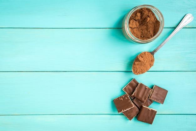 Плитка молочного шоколада и какао на синем деревянном фоне.