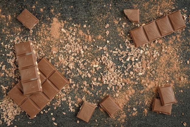 Плитка молочного шоколада, шоколадная стружка и какао на черной поверхности
