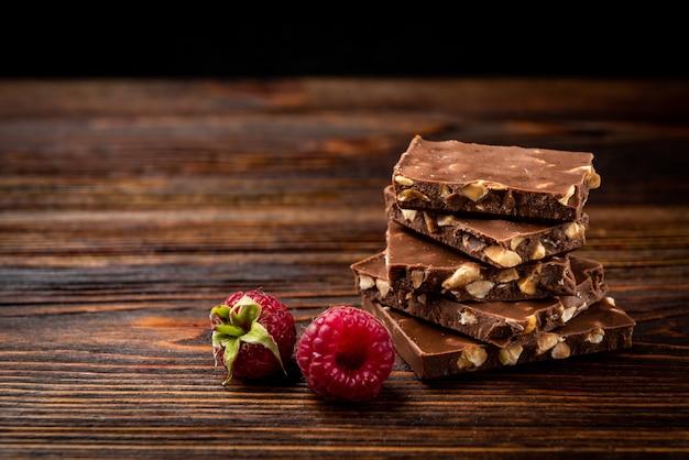 Плитка молочного шоколада с малиной на темном деревянном столе.