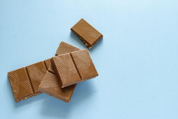 Кусочки молочного шоколада, изолированные на синем фоне, вид сверху закройте изолированную плитку шоколада