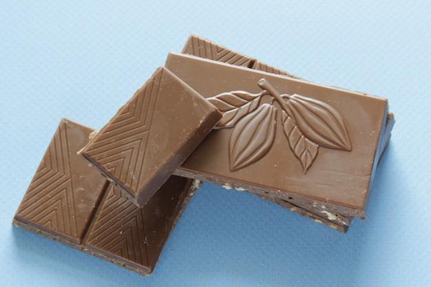 상위 뷰에서 파란색 배경에 격리된 밀크 초콜릿 조각 초콜릿 바를 닫습니다