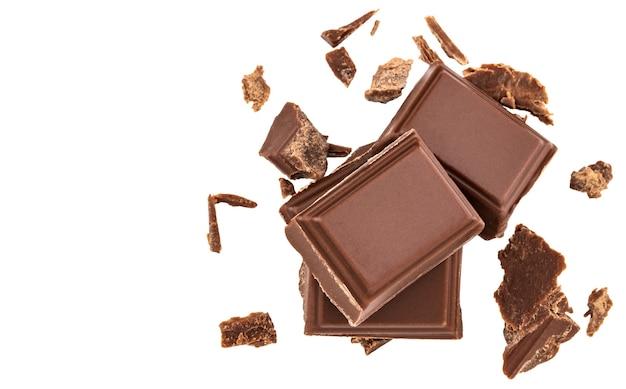 Кусочки молочного шоколада, изолированные на белом фоне, вид сверху.
