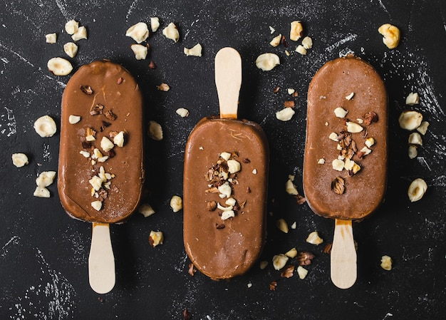 Milk chocolate popsicles with hazelnuts. close-up. ice cream popsicles covered with chocolate, sticks, black stone background.