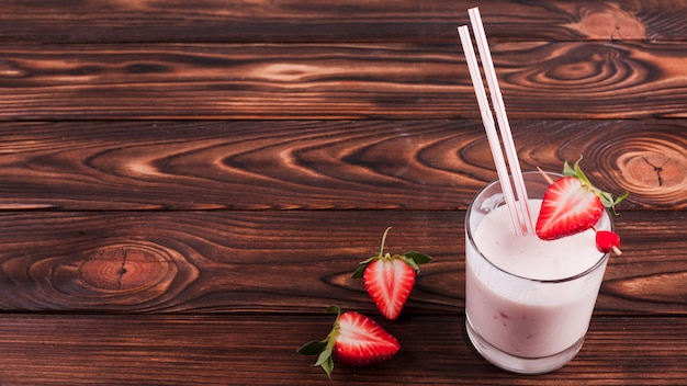 Milk cocktail with strawberry on wooden surface