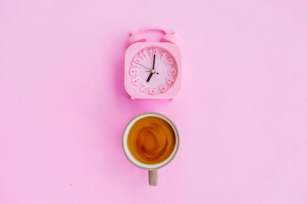 분홍색 배경에 격리된 우유 커피와 알람 시계, 최소한의 개념 아이디어.