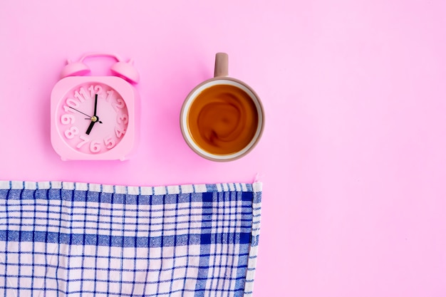 분홍색 배경에 격리된 우유 커피, 파란색 천, 알람 시계, 최소한의 개념 아이디어.