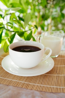 Milk and coffee cup on bamboo mat