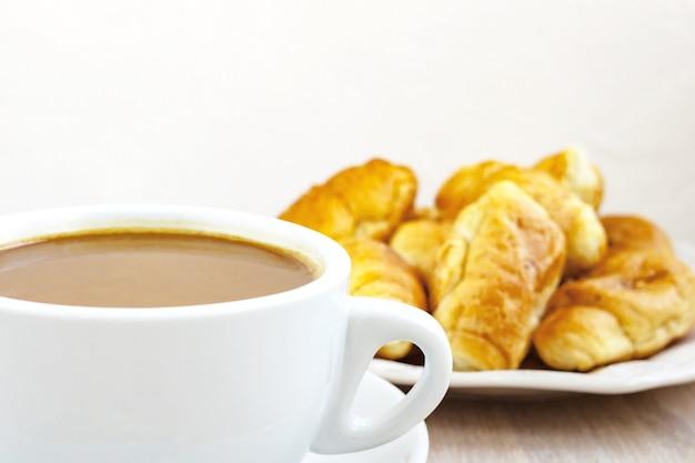 軽い木製の受け皿とクロワッサンとミルクコーヒーカップのクローズアップ。朝食のコンセプト。セレクティブフォーカス。コピースペース
