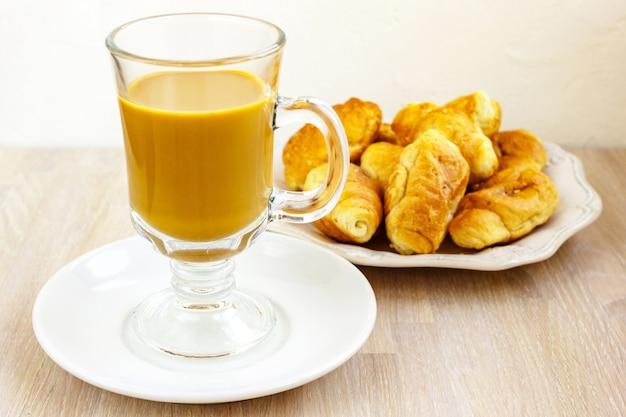ミルクコーヒーグラスカップとライトウッドのクロワッサンの白いプレートをクローズアップ。朝食のコンセプト。セレクティブフォーカス。コピースペース