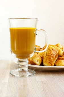 Milk coffee gluss cup and white plate of croissants on light wooden  close up. breakfast concept. selective focus. copy space