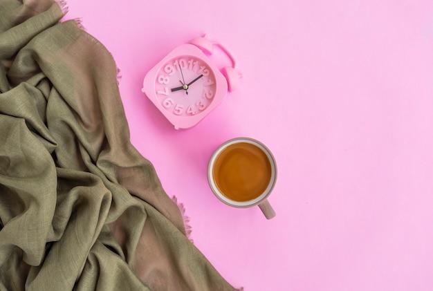 분홍색 배경에 격리된 우유 커피, 녹색 스카프, 알람 시계, 최소한의 개념 아이디어.