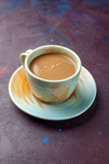 暗いナス色の机の上のカップの中のミルクコーヒー