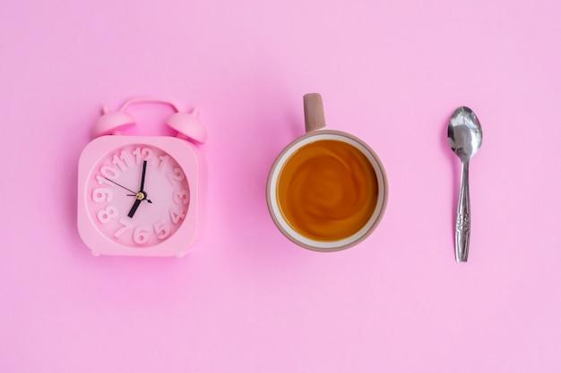 분홍색 배경에 격리된 우유 커피, 숟가락, 알람 시계, 최소한의 개념 아이디어.
