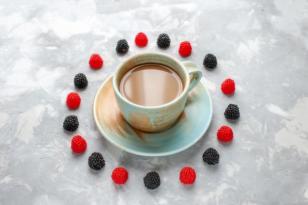 Caffè al latte con confettura di frutti di bosco sulla scrivania grigio-bianco caramelle caffè zucchero dolce
