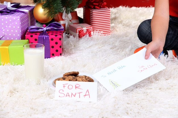 クリスマスツリーの下のサンタクロースのためのミルク、クッキー、手紙