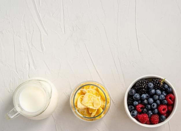 우유, 콘플레이크, 신선한 딸기-흰색 배경에 간식이나 아침 식사 재료. 평평하다, 복사 공간, 텍스트를위한 공간. 위에서 봅니다.