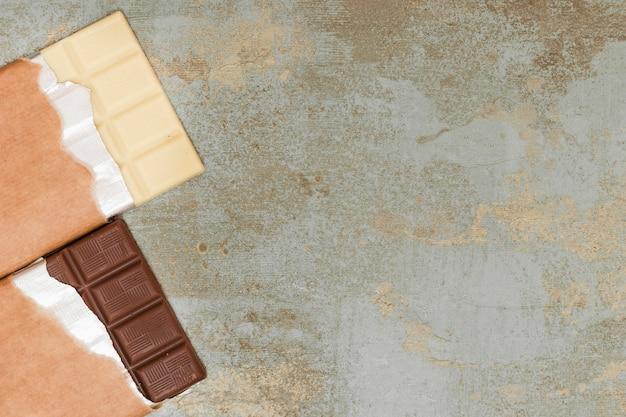 Milk and dark chocolate bar on grunge background