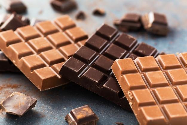 Milk and dark chocolate bars on a grey table