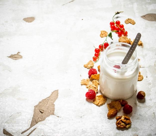 Молочный десерт с хлопьями, орехами и лесными ягодами на деревенском фоне
