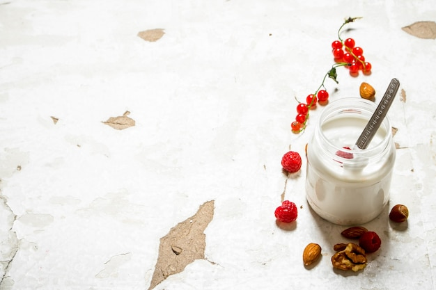Milk dessert with nuts and wild raspberries on rustic background