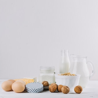 Milk; eggs; bowl of cereals; cheese and walnuts on white backdrop