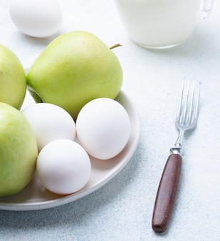 Milk, flour, eggs and green apples on a white background. ingredients for apple charlotte. recipe