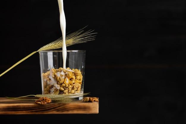 Молоко вливается в зерновые мюсли в прозрачном стакане с ржаным колосом и грецкими орехами на полке на черном фоне. скопируйте пространство.