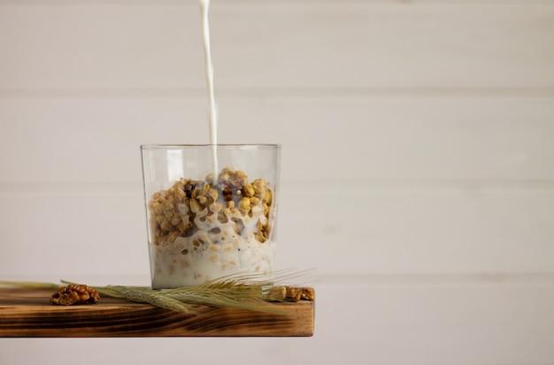 Молоко течет в зерновые мюсли в прозрачном стакане с шипом ржи и грецкими орехами на полке на белом фоне. скопируйте пространство.