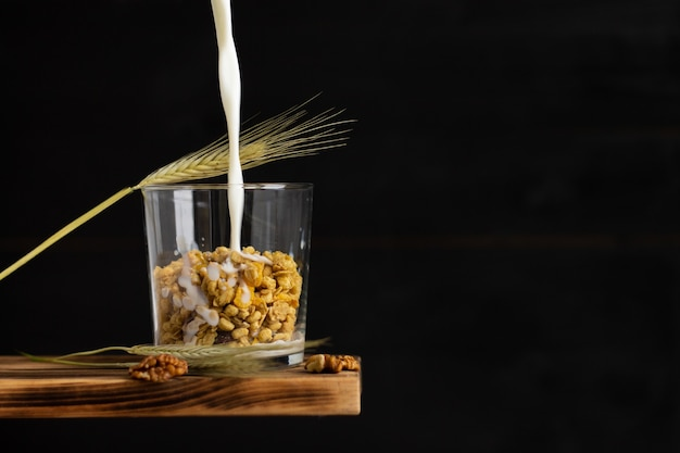 Milk flowing into a cereal granola in a transparent glass with rye spike and walnuts on a shelf on a black background. copy space.
