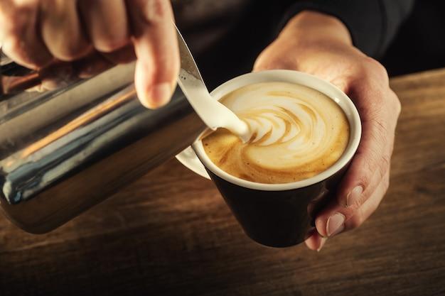 ミルクフォームをカップに注ぎ、完璧なカプチーノを形成します-コーヒーアート。