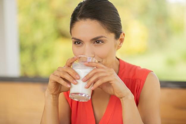 朝食用のミルク。朝食にミルクを飲みながら思慮深く感じている美しい暗い目の女性